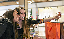 Two female friends taking a selfie at shopping center - MGOF001265