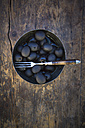 Bowl of black olives and fork on dark wood - LVF004409