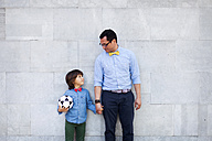 Father and son holding hands, boy holding soccer ball - VABF000049