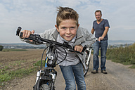 Portrait of little boy on bicycle tour with his father in the background - PAF001528