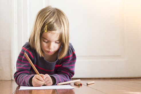 Little girl lying on the floor drawing something - LVF004419