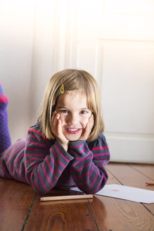 Portrait of little girl lying on the floor with paper and coloured pencils - LVF004422
