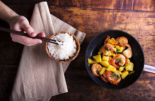 Frying pan of prawns with pineapple and man's hand taking rice with chopsticks - HAPF000167