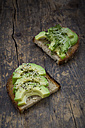 Slice of toasted bread with acocado, cress and hemp seeds on wood - LVF004426