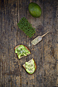 Slice of toasted bread with acocado, cress and hemp seeds on wood - LVF004429