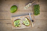 Slice of toasted bread with acocado, cress and hemp seeds on wooden board - LVF004435