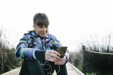 Young woman relaxing after running, using smartphone - JRFF000338