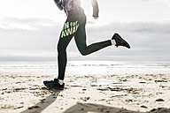 Spain, Tarragona, Legs and sneakers running in the sand of a beach - JRFF000341