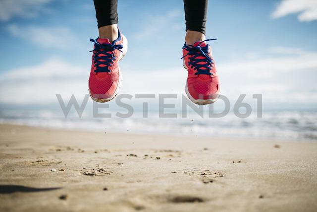 Feet of woman jumping on beach - JRFF000344 - Josep Rovirosa/Westend61