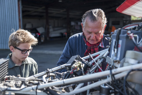 Germany, Dierdorf, Grandfather and grandson repairing biplane - PAF001545