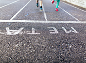 Legs of two running girls on tarmac - MGOF001274