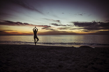 USA, Florida, Naples, Silhouette of woman doing yoga at beach, sunset - CHPF000196