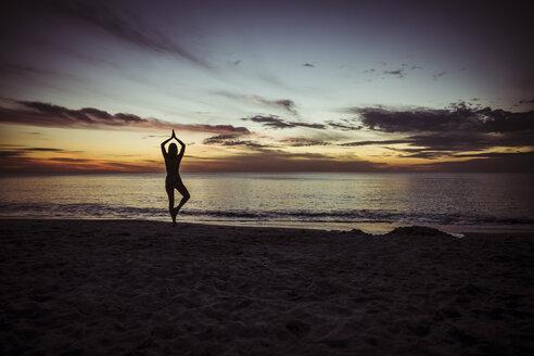 USA, Florida, Naples, Silhouette of woman doing yoga at beach, sunset - CHPF000196