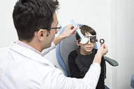 Optometrist examining eyesight of boy - ERLF000101