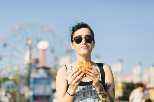 USA, New York, Coney Island, young woman eating a hamburger - GIOF000627