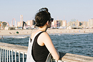 USA, New York, Coney Island, young woman relaxing on pier - GIOF000633