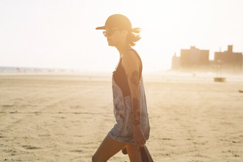 USA, New York, Coney Island, young woman on the beach at sunset - GIOF000636