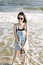 USA, New York, Coney Island, portrait of happy young woman wading in the sea - GIOF000651