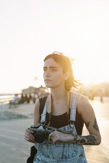 USA, New York, Coney Island, young woman  taking photos at sunset - GIOF000669
