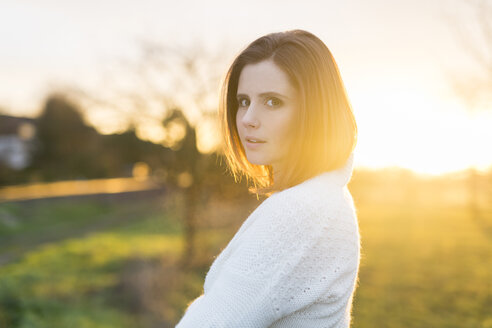Portrait of brunette woman in field at sunrise - SHKF000456