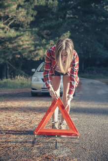 Young woman putting warning triangle on country lane by vehicle breakdown - DAPF000010