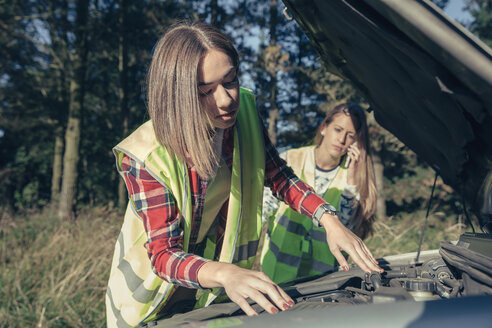 Two young women wearing safety vests at damaged car - DAPF000013