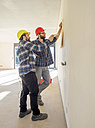 Two craftsmen discussing plan in construction site - LAF001590
