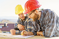 Two craftsmen discussing and taking notes in construction site - LAF001593