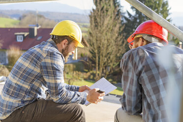 Two craftsmen looking at notes in construction site - LAF001596