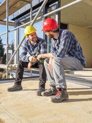 Two craftsmen clinking beer bottles in construction site - LAF001599