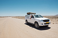 Namibia, Namib desert, Swakopmund, man on a 4x4 car with tent on the roof in a dusty road - GEMF000632