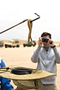 Namibia, Namib desert, Swakopmund, tourist taking pictures of a Sidewinder Snake in a desert expedition - GEM000635