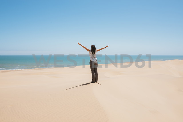 Namibia, Namib desert, Swakopmund, woman in the desert with the sea in the background - GEMF000641