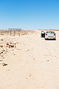 Namibia, Namib desert, Swakopmund, empty car with open door in a dusty track next to the Tropic of Capricorn sign - GEMF000644