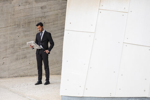 Businessman wearing black suit reading newspaper - SIPF000082