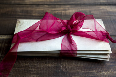 Stack of old love letters tied with red ribbon - SARF002457