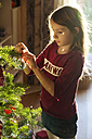 Girl decorating Christmas tree - SARF002465