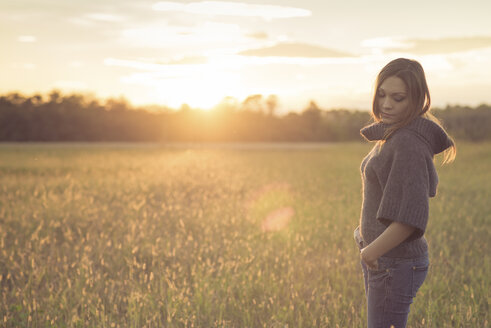 Woman wearing turtleneck pullover standing on a meadow at backlight - SIPF000098