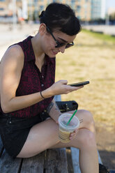 Young woman sitting on a bench with plastic cup looking at her smartphone - GIOF000686