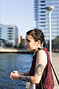 USA, New York City, Williamsburg, tattooed young woman leaning on a railing - GIOF000695
