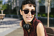 Portrait of young woman with headphones wearing sunglasses - GIOF000704
