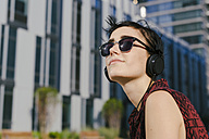 Portrait of young woman with headphones and sunglasses - GIOF000707