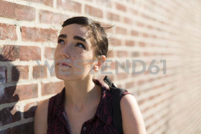 Portrait of young woman leaning against brick wall - GIOF000710