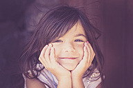 Portrait of smiling girl with head in her hands - SIPF000099