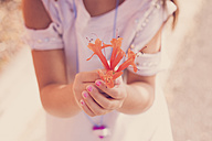 Girl holding orange blossom in her hands, close-up - SIPF000102