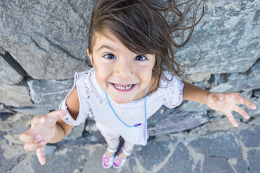 Portrait of staring little girl with blowing hair in front of a rock face - SIPF000105