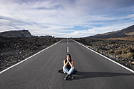 Spain, Tenerife, woman with closed eyes sitting on an empty road - SIPF000113