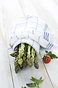 Bunch of green asparagus wrapped in kitchen towel - ASF005810