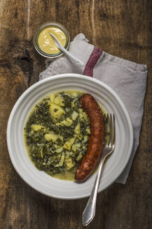 Green cabbage, potatoes and minced pork sausage on plate, mustard and fork - ODF001358