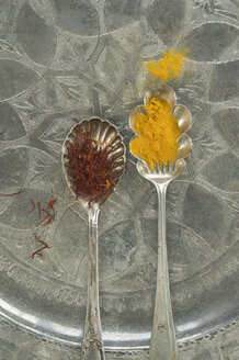 Silver spoons of ground saffron and saffron threads on silver tray - ASF005813